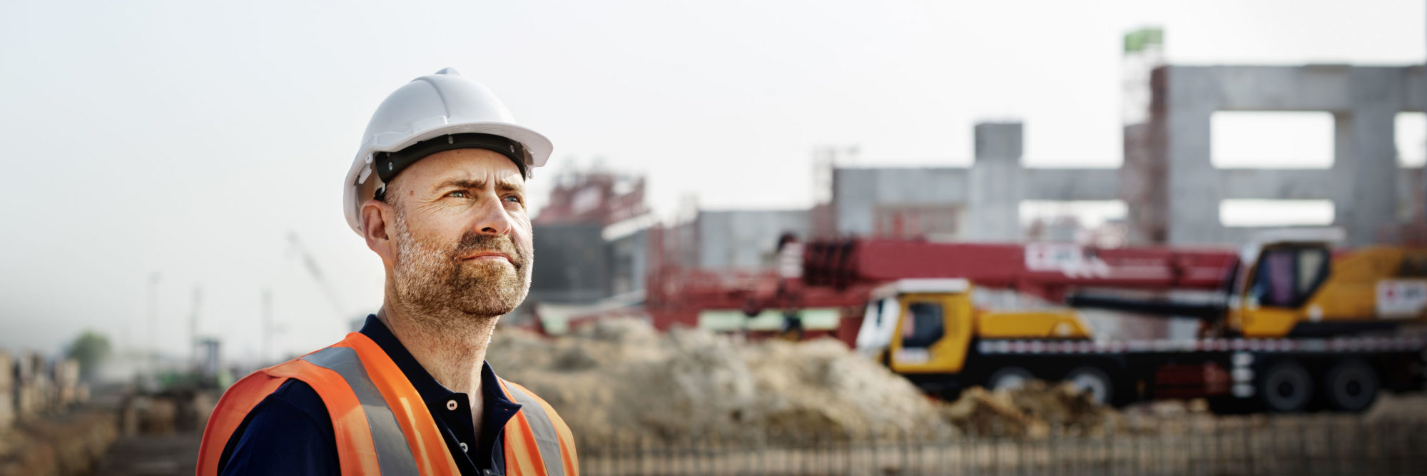 Person på byggarbetsplats med hjälm och väst, blickar möjligen ut över bygget.