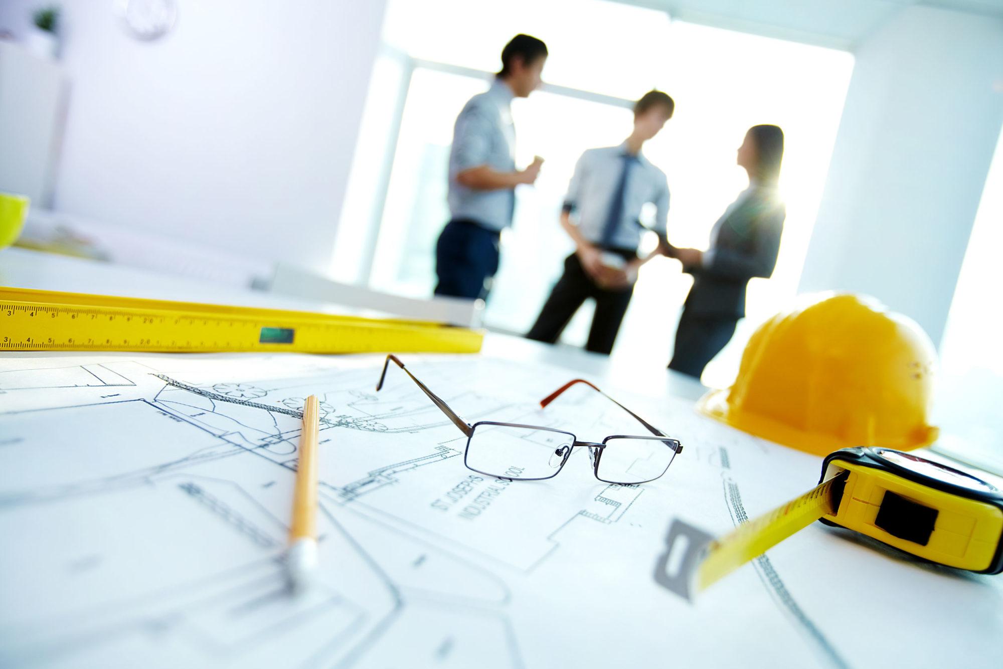 Skiss av planlösning med penna, måttstock och glasögon ovanpå, tre personer diskuterar i bakgrunden.