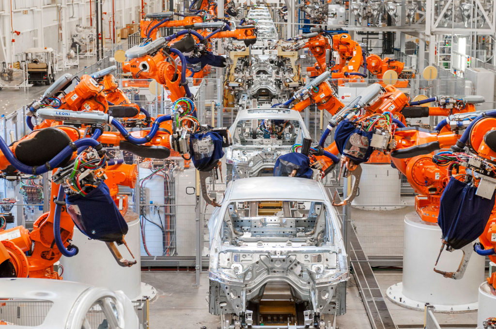 Flertal industrirobotar som i ett led sätter ihop bilar.