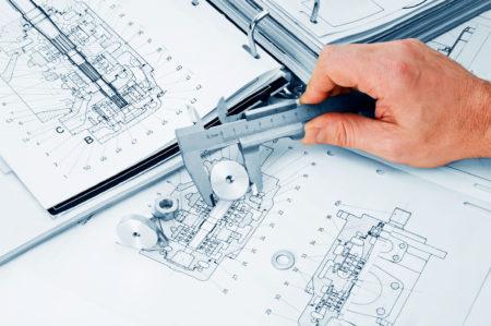 Hand över olika ritningar som använder ett mätinstrument för att mäta en mutter.
