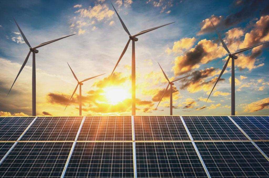 Solceller och vindkraftverk framför solnedgång