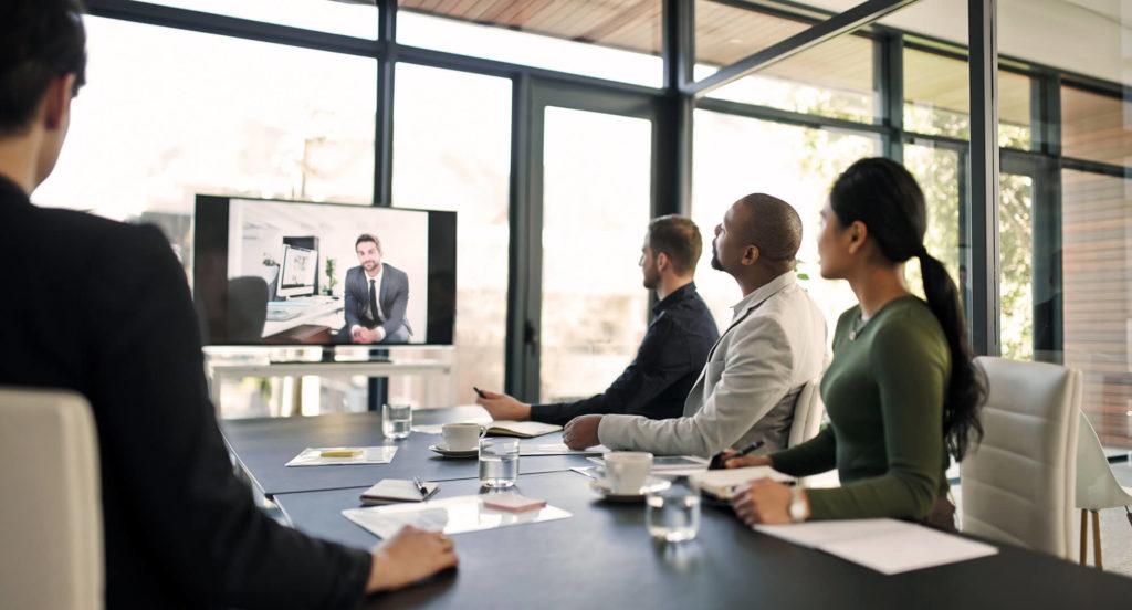 Personer vid ett bord kollar på en TV