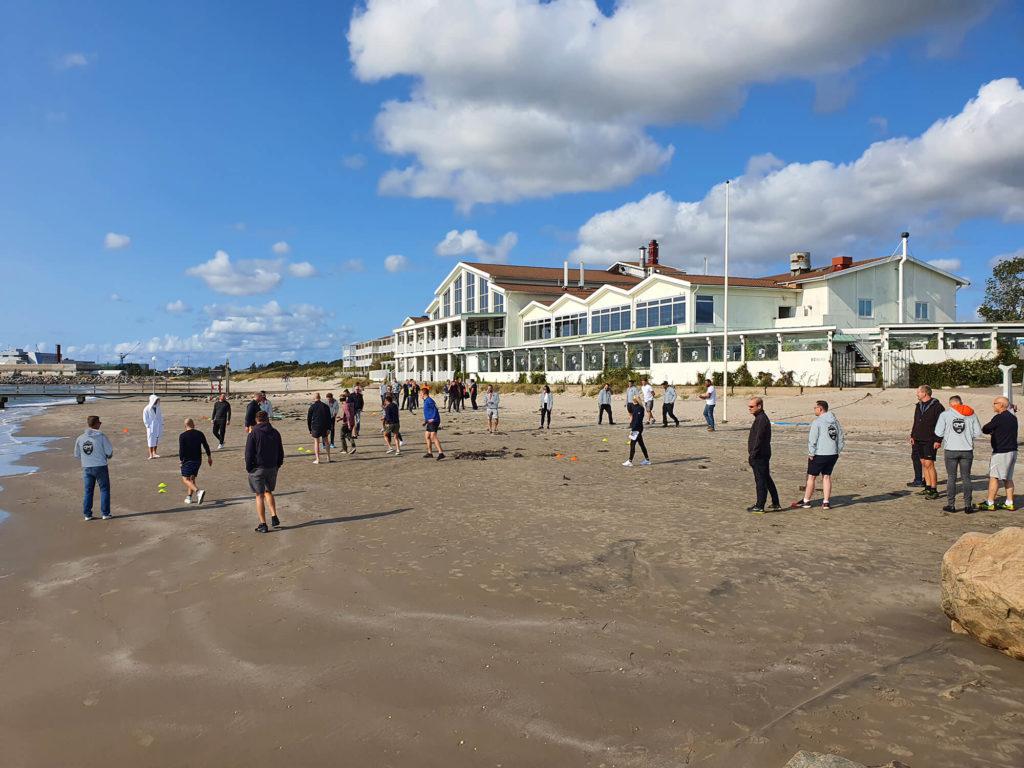 Personer på strand framför stort hus