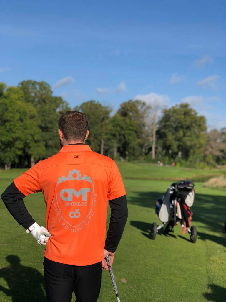 Person i OMT-tröja spelar golf