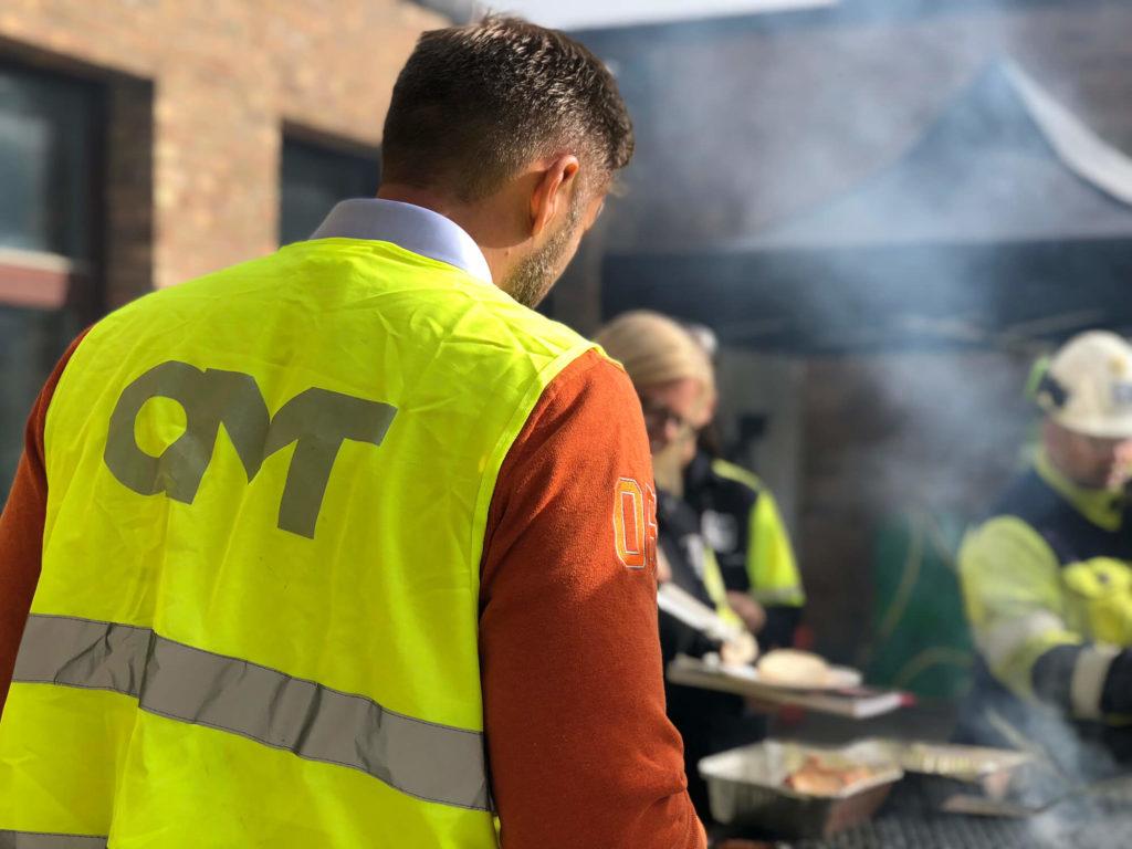 Personer i OMT-västar grillar
